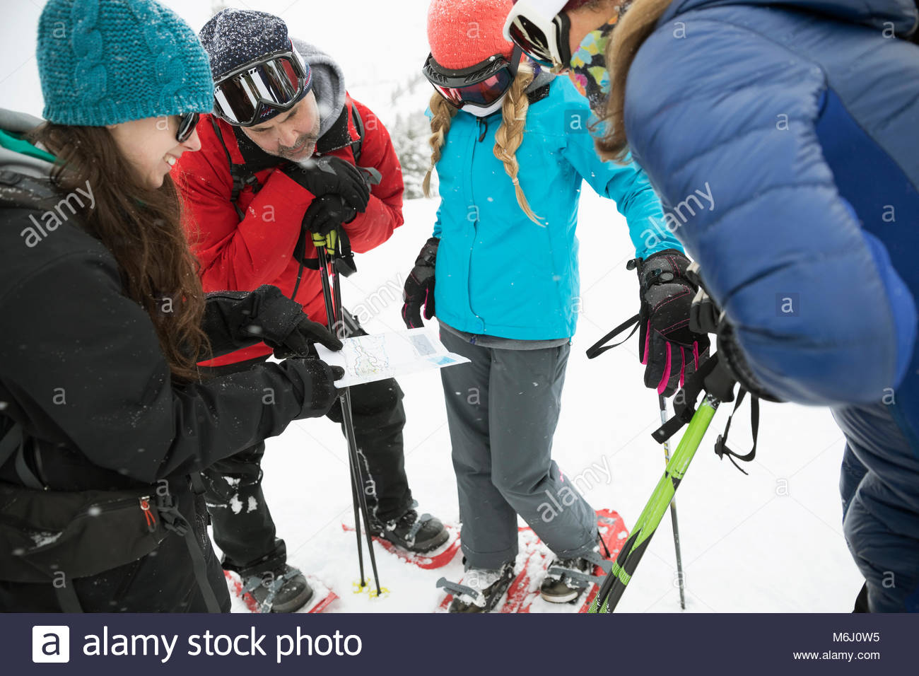 Family snowshoeing, checking map - Stock Image
