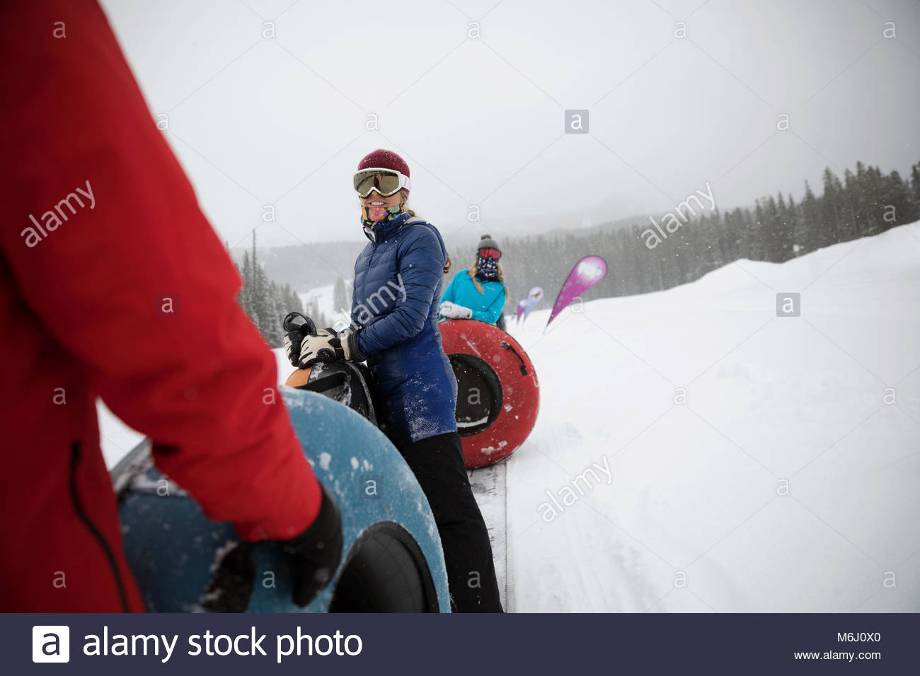 Family inner tubing in snow at tube park - Stock Image
