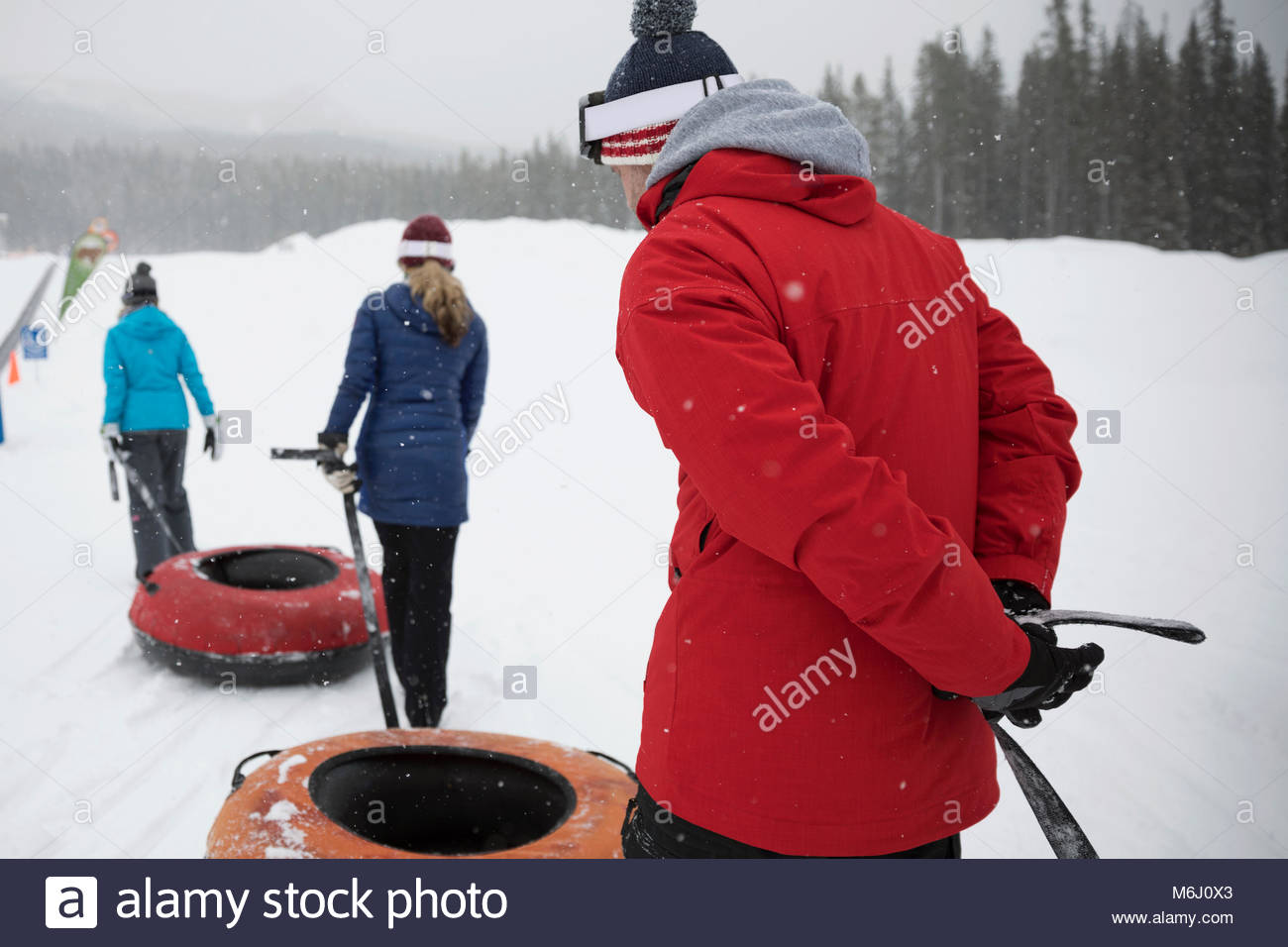 Family pulling inner tubes in snow at tube park - Stock Image