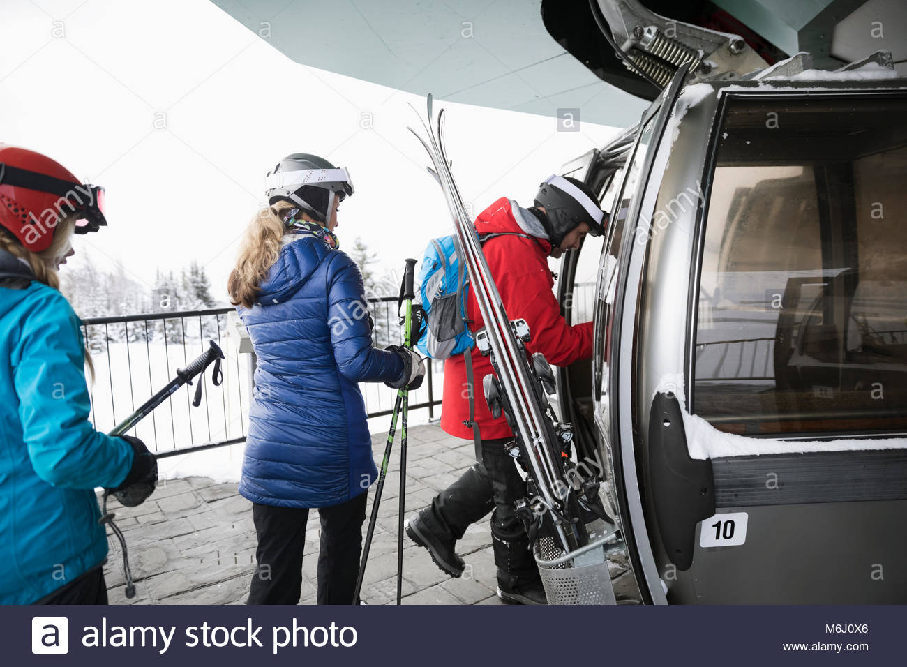 Family skiers getting into gondola at ski resort - Stock Image
