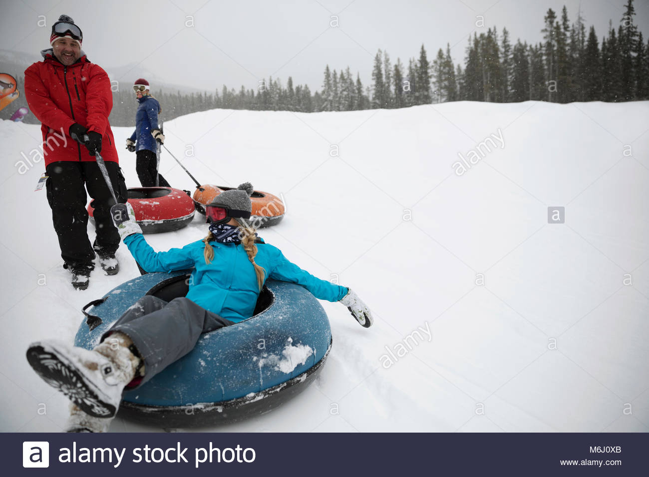 Playful family inner tubing in snow at tube park - Stock Image