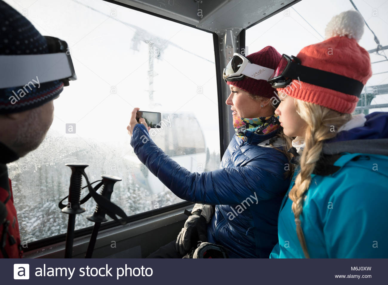 Family skiers riding gondola, photographing view with camera phone - Stock Image