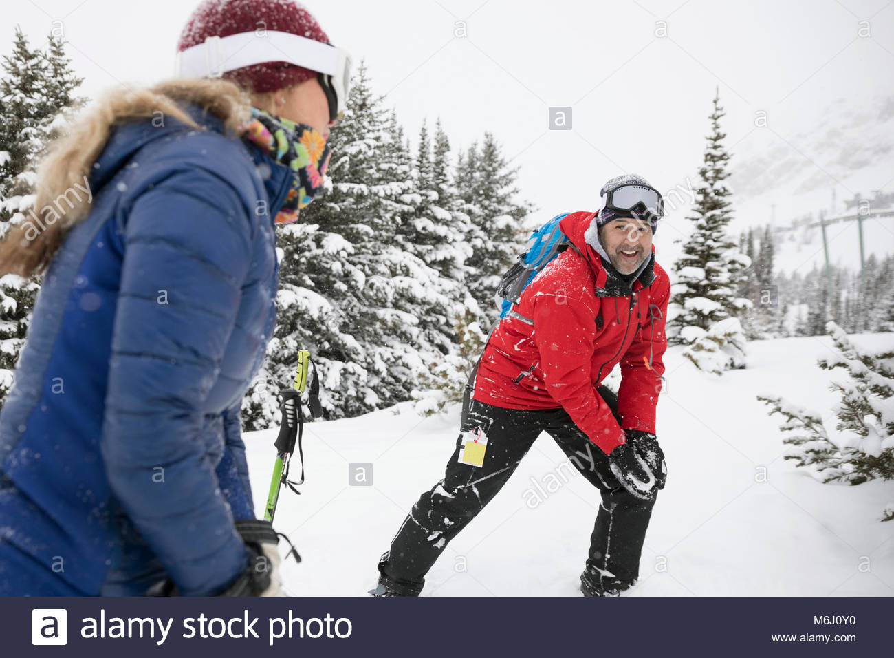 Playful couple snowshoeing, enjoying snowball fight in snow - Stock Image