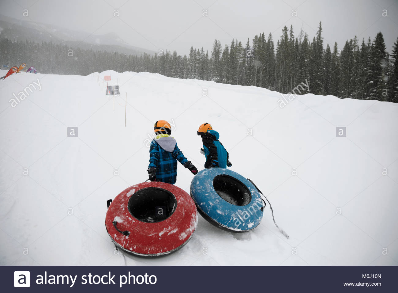 Brothers pulling inner tubes in snow at tube park - Stock Image