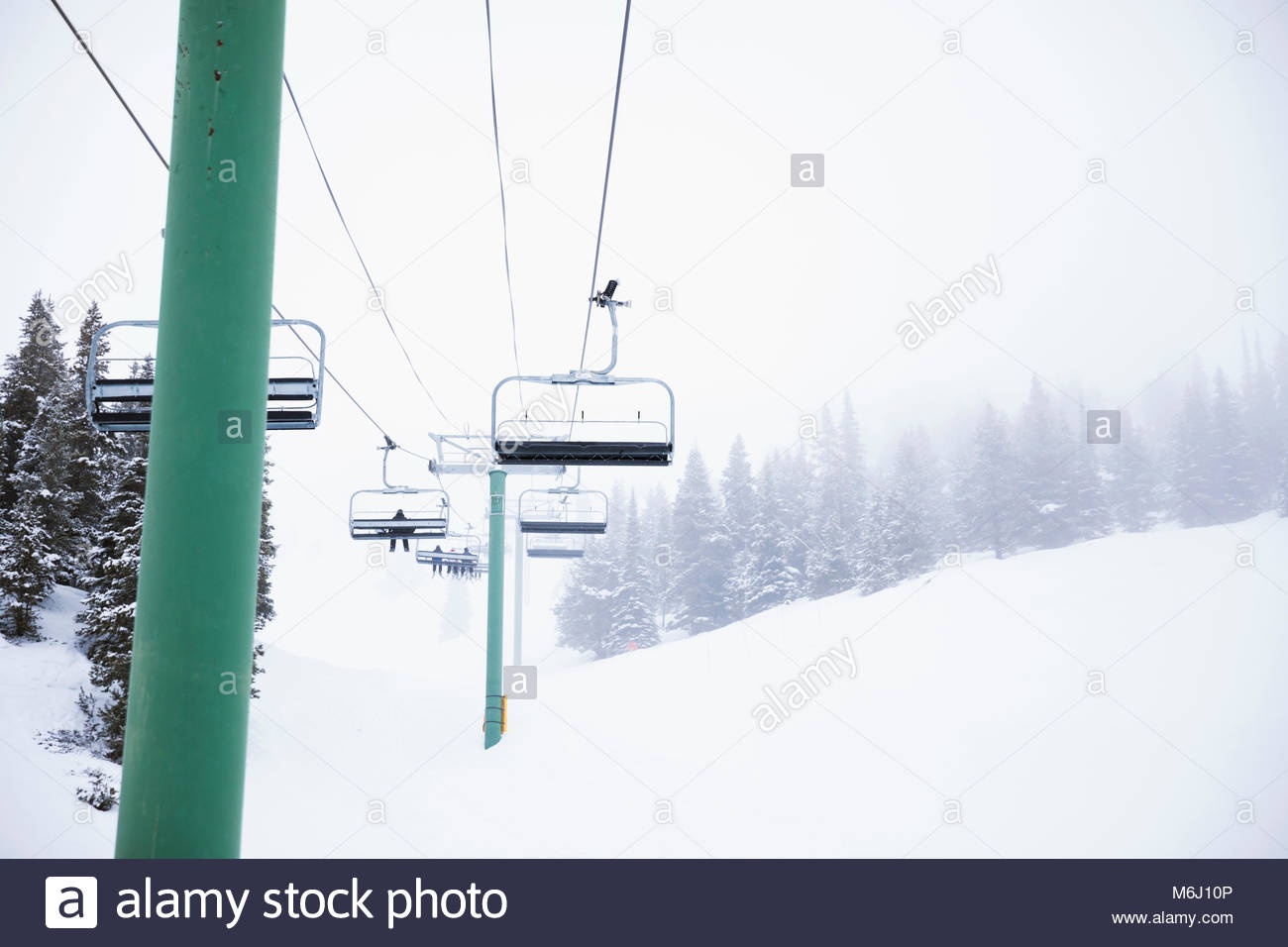 Skiers on chair lift over snowy landscape at ski resort - Stock Image