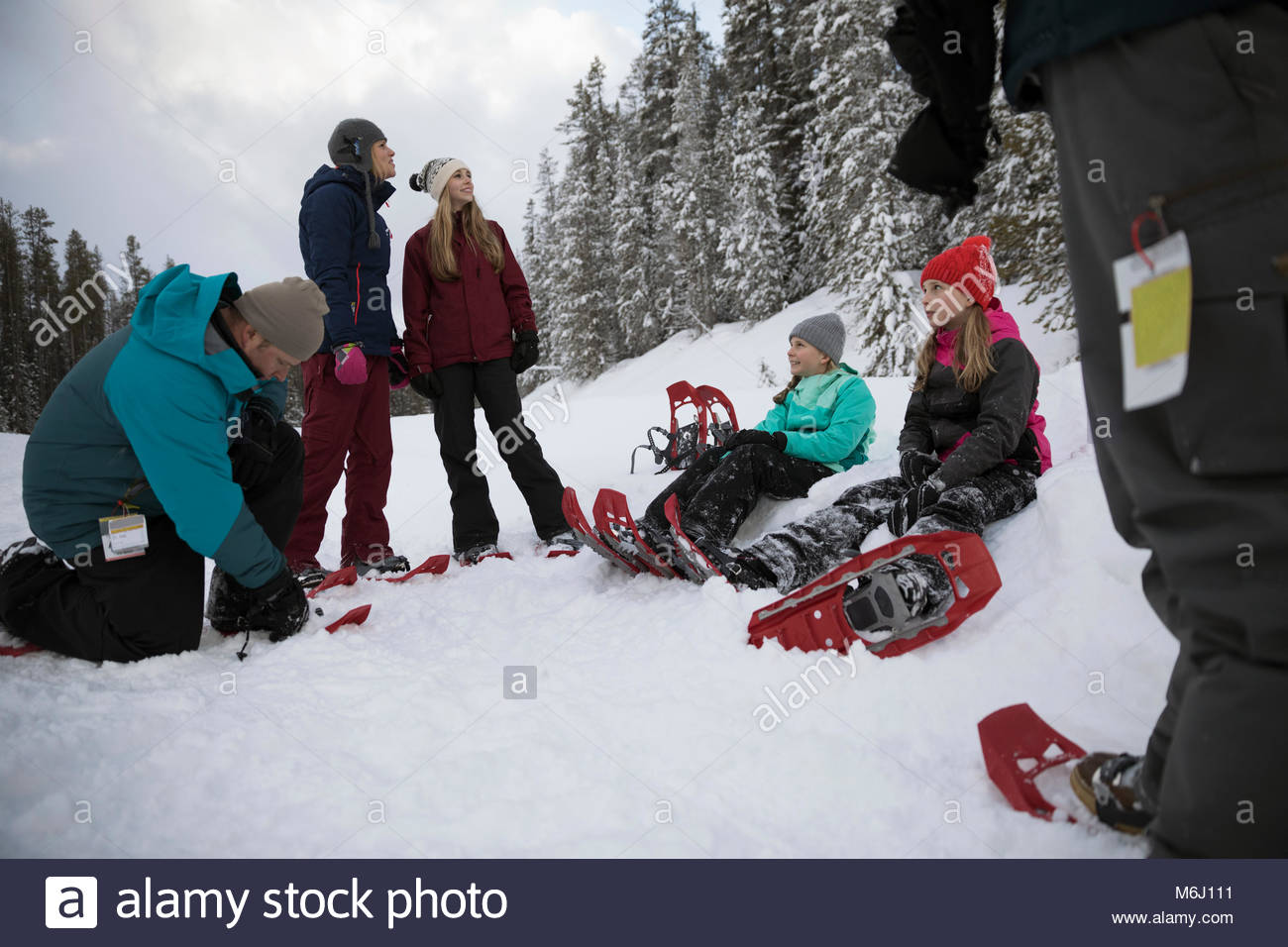Family preparing for snowshoeing, putting on snowshoes in snow - Stock Image