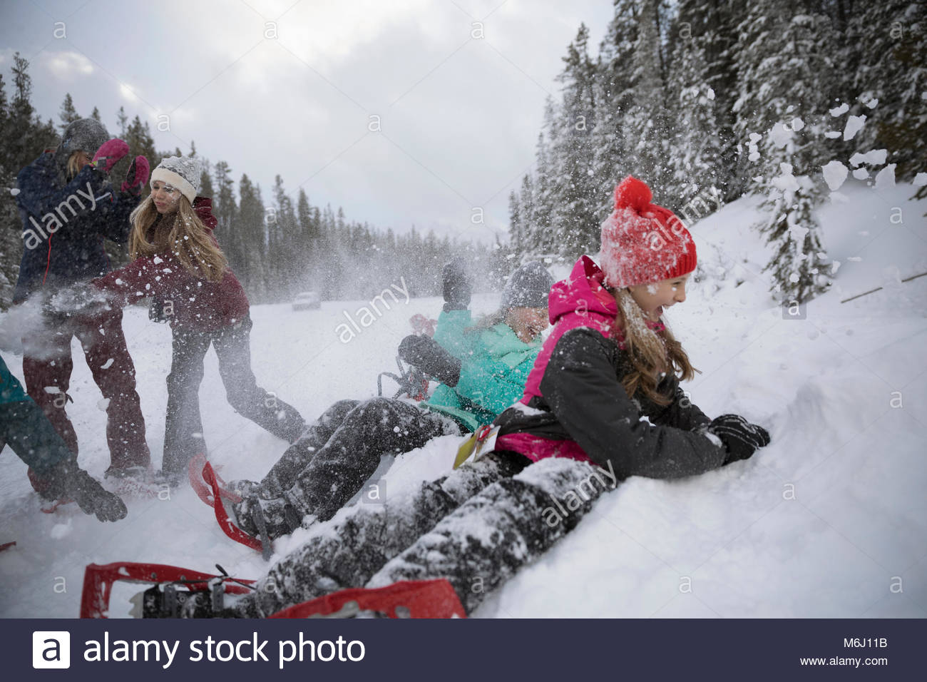 Playful family snowshoeing, enjoying snowball fight - Stock Image