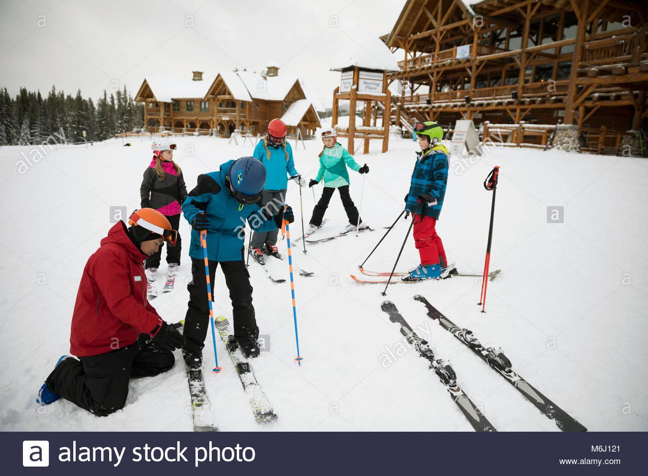 Ski instructor fastening skis on boy student at ski resort - Stock Image