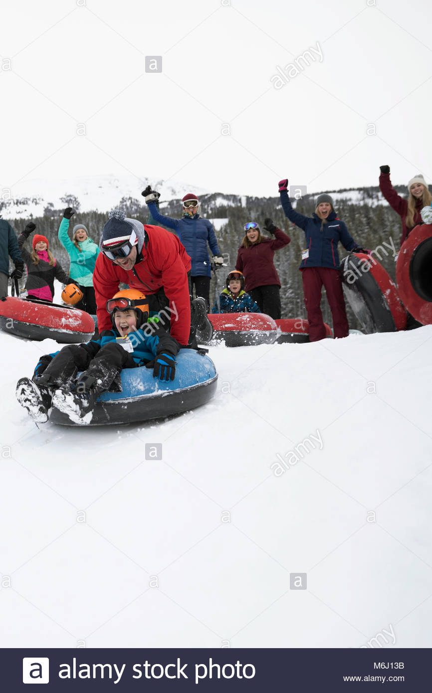 Family cheering father pushing son on inner tube in snow - Stock Image