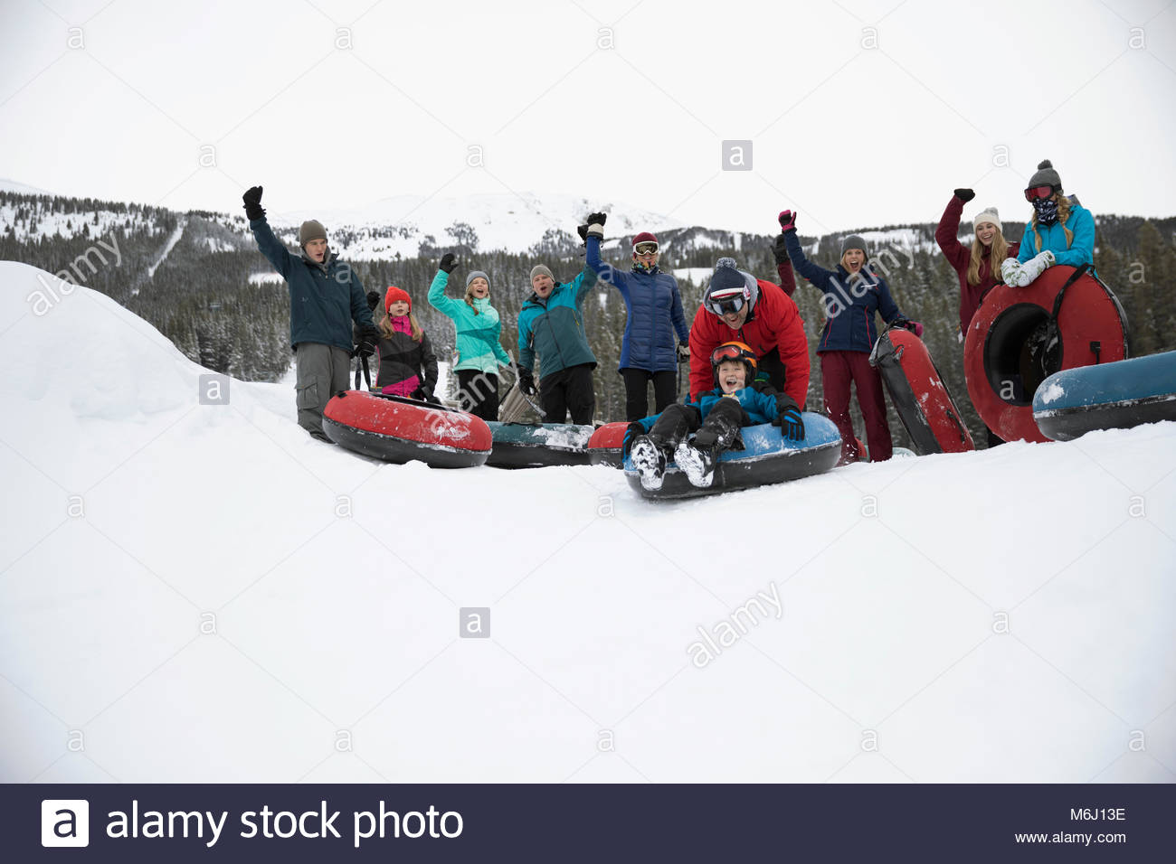 Portrait family cheering, inner tubing in snow at snow park - Stock Image