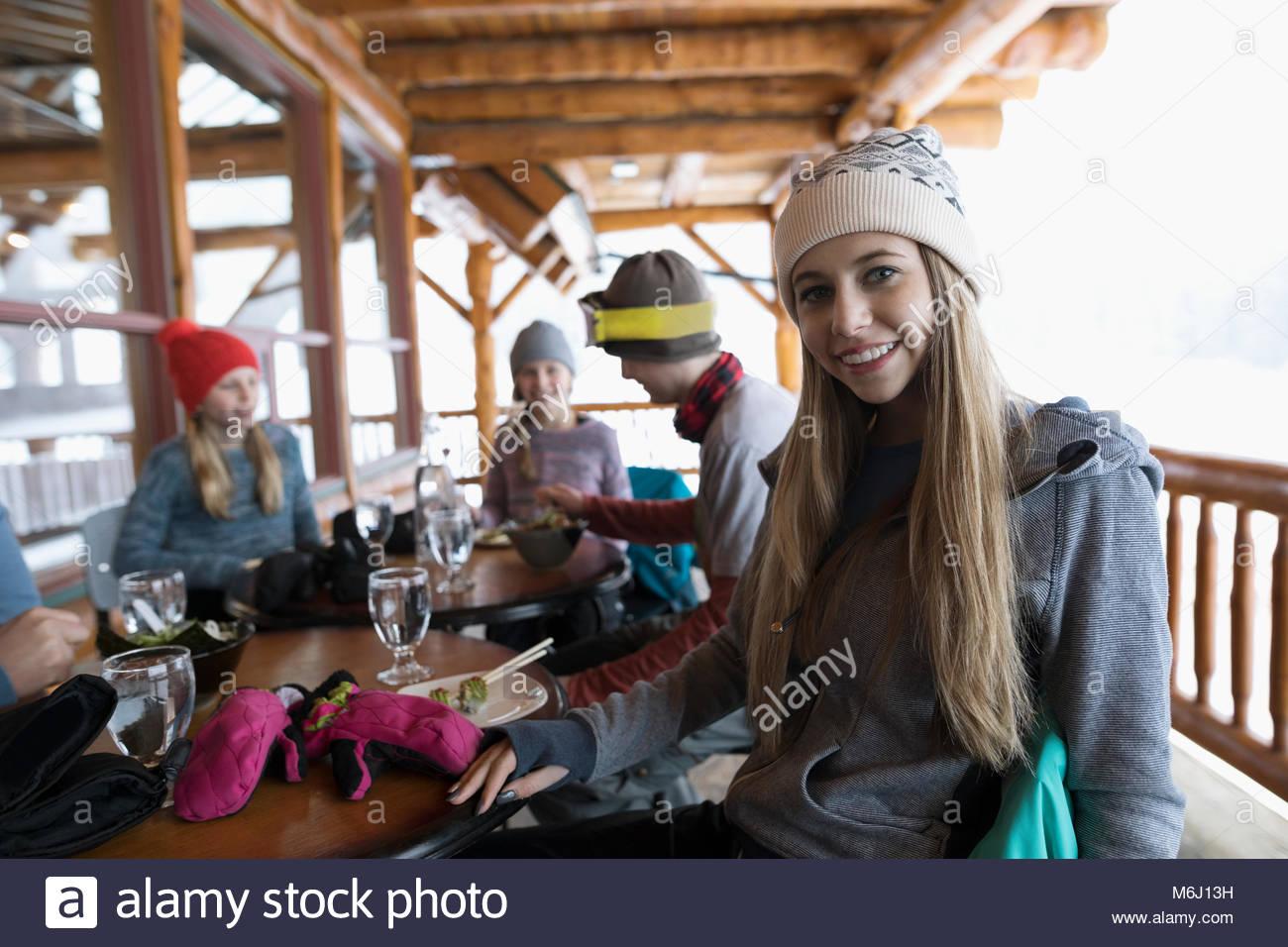 Portrait smiling, confident teenage girl skier eating with family apres-ski on ski resort lodge balcony - Stock Image