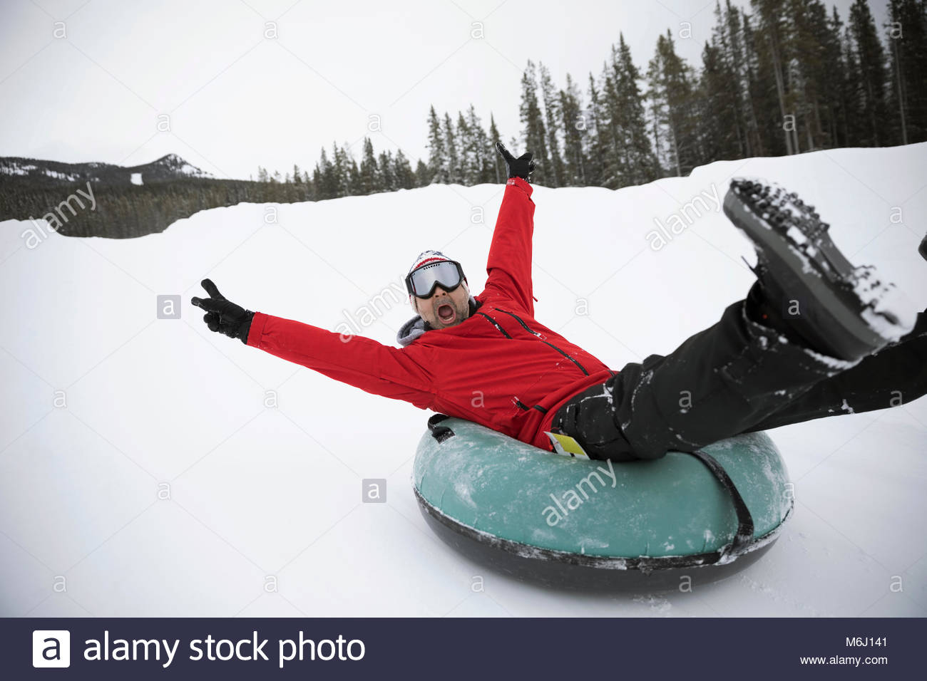 Portrait playful, exuberant man inner tubing in snow at tube park - Stock Image