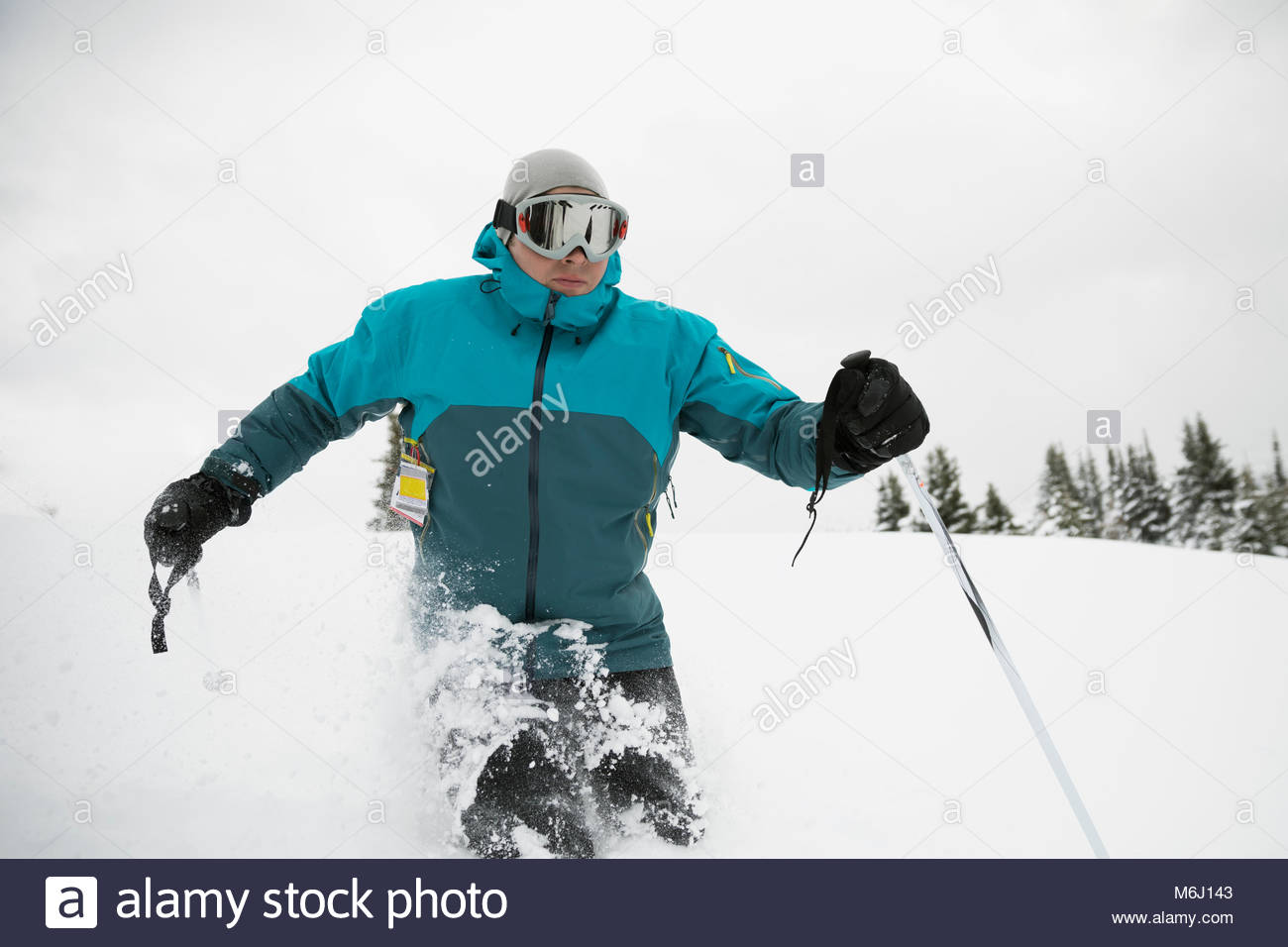 Male skier skiing in snow - Stock Image