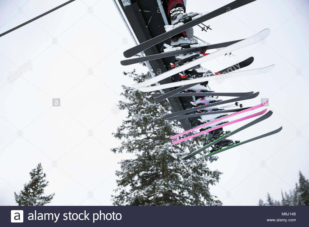 Skier skis dangling from chair lift - Stock Image
