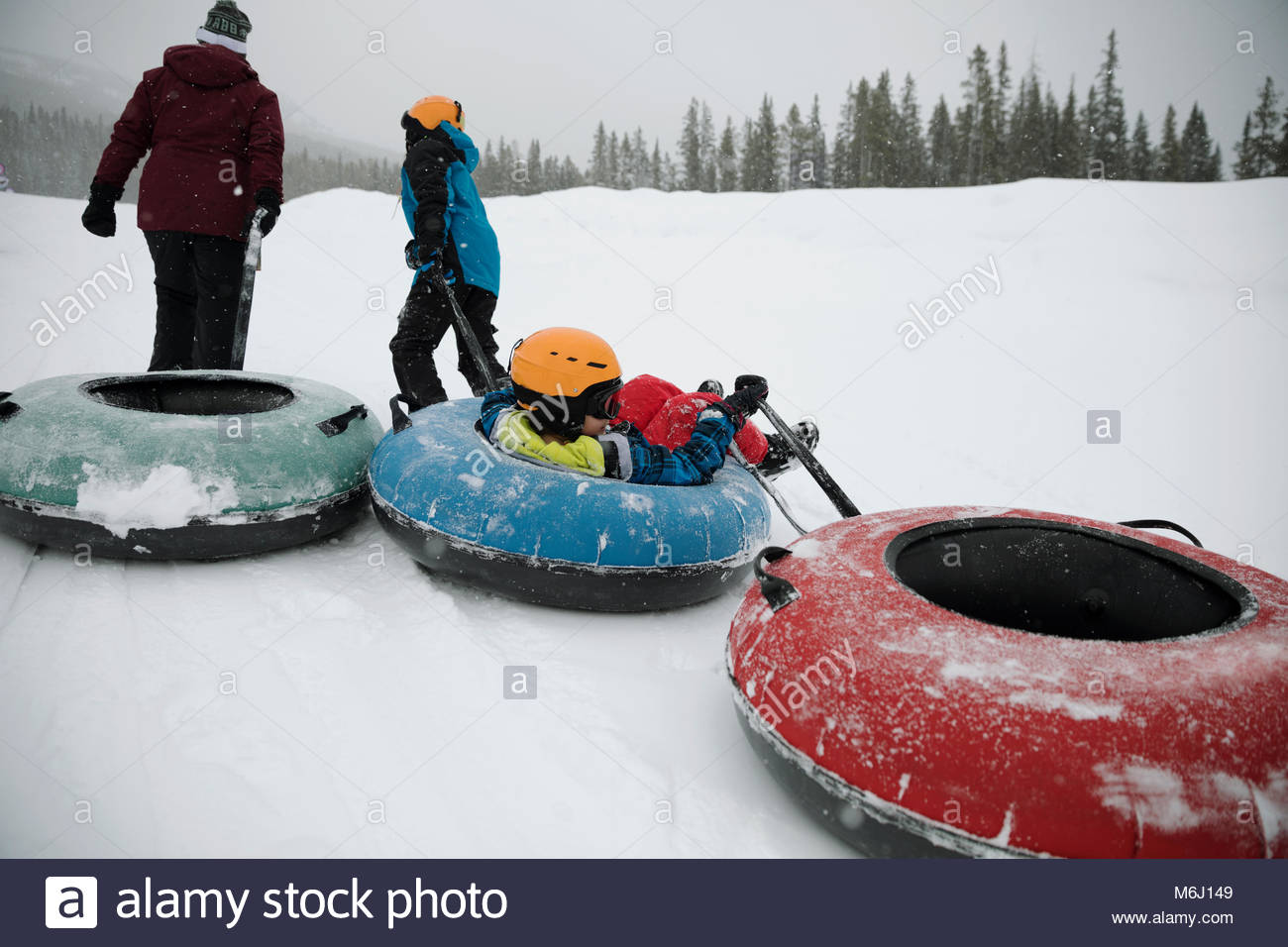 Boy pulling brother in inner tube in snow at tube park - Stock Image