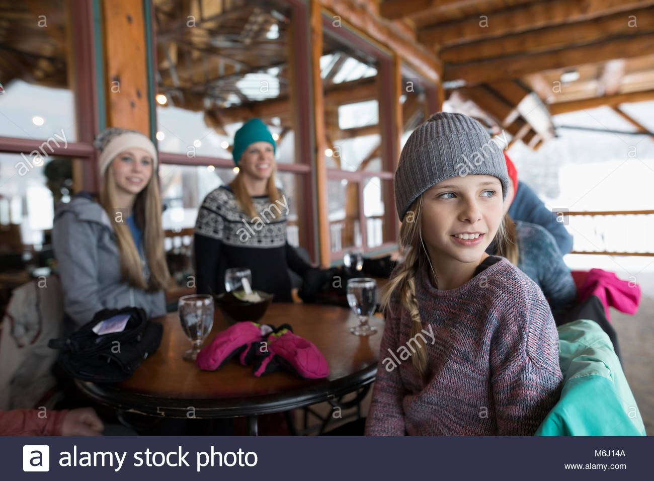 Curious girl skier with family sitting on ski resort lodge balcony apres-ski - Stock Image