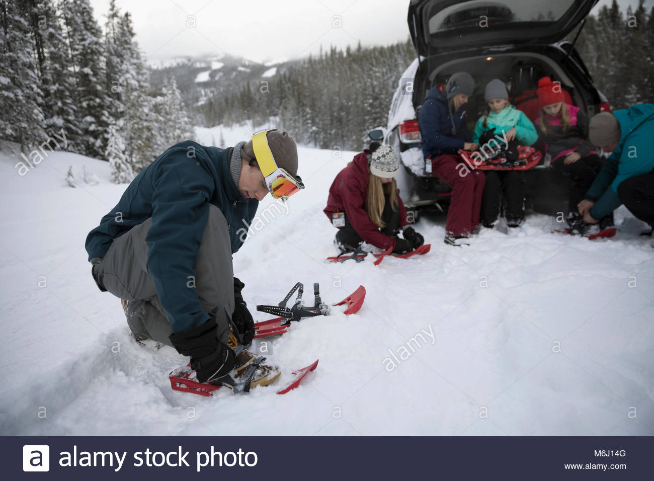 Family preparing for snowshoeing at car in remote snow - Stock Image