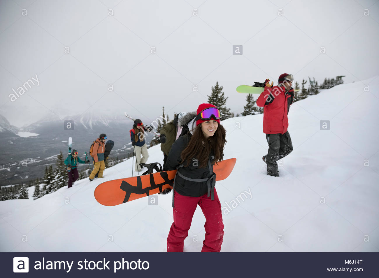 Skiers and snowboarders hiking snowy hill - Stock Image