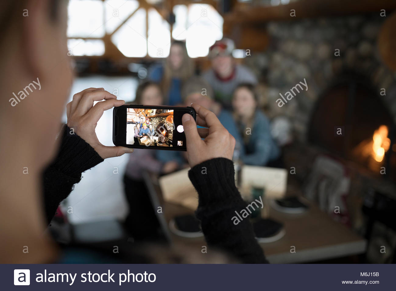 Woman photographing family skiers at ski resort lodge fireside apres-ski - Stock Image
