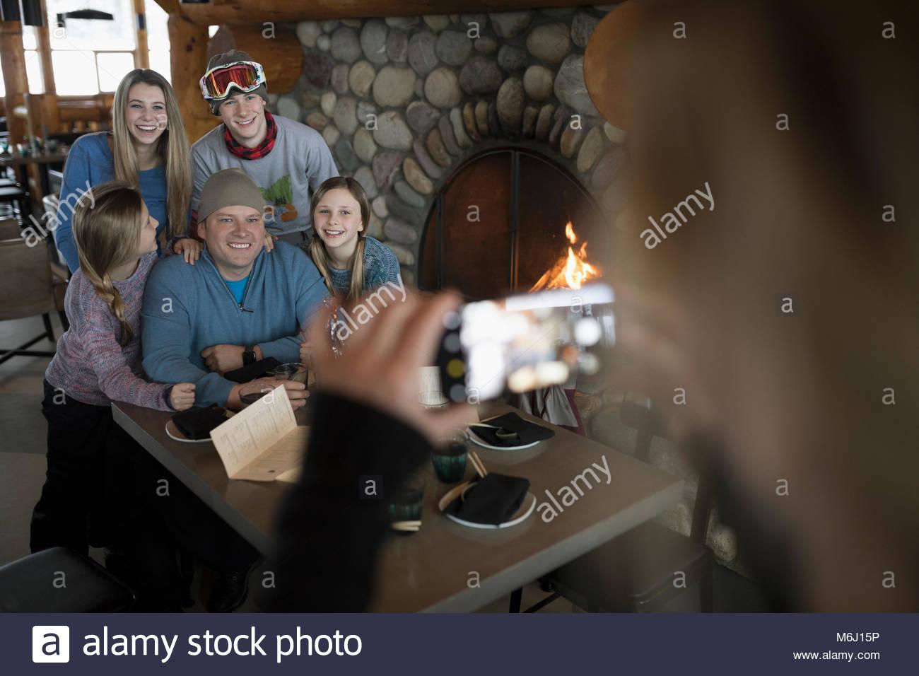 Woman photographing family skiers at ski resort lodge fireside apres-ski - Stock Image