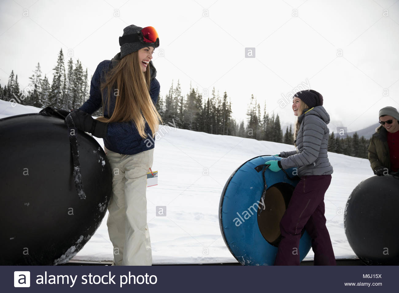 Friends carrying inner tubes in snow - Stock Image
