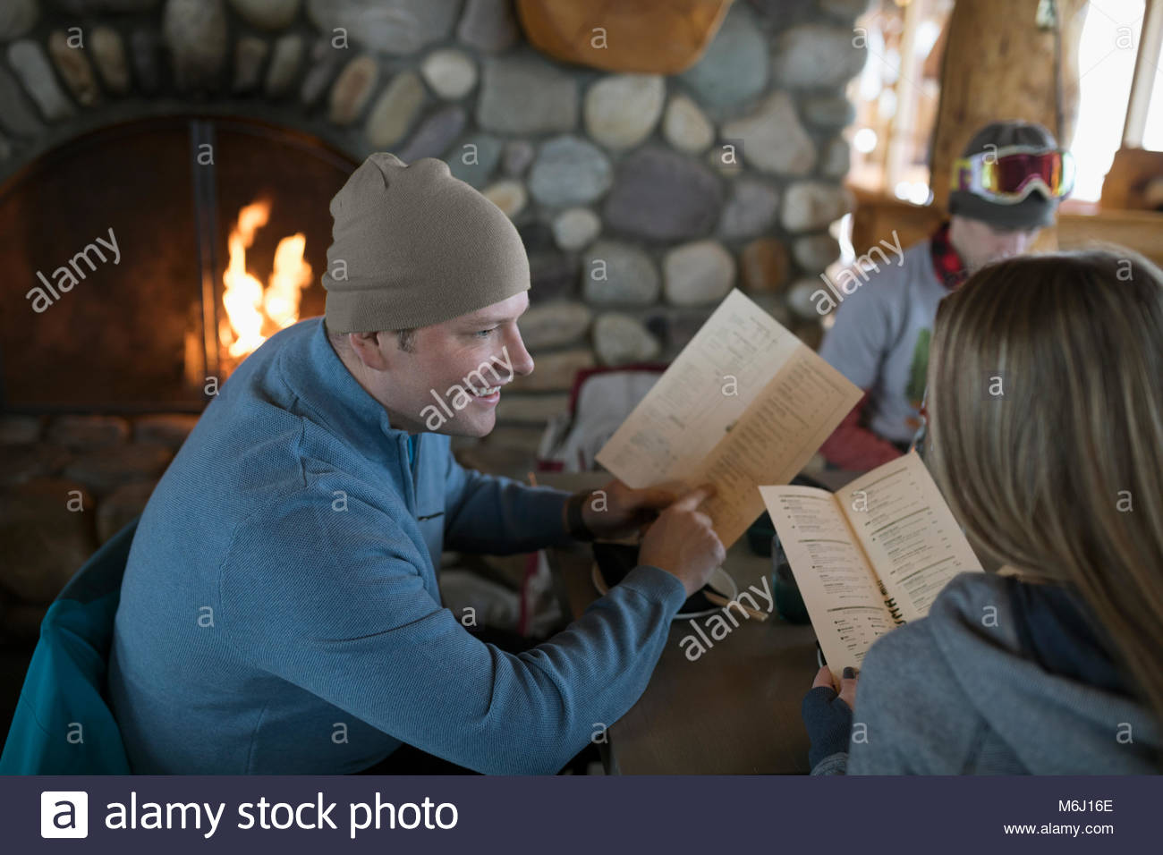 Father and daughter skiers looking at ski resort lodge restaurant menu fireside apres-ski - Stock Image