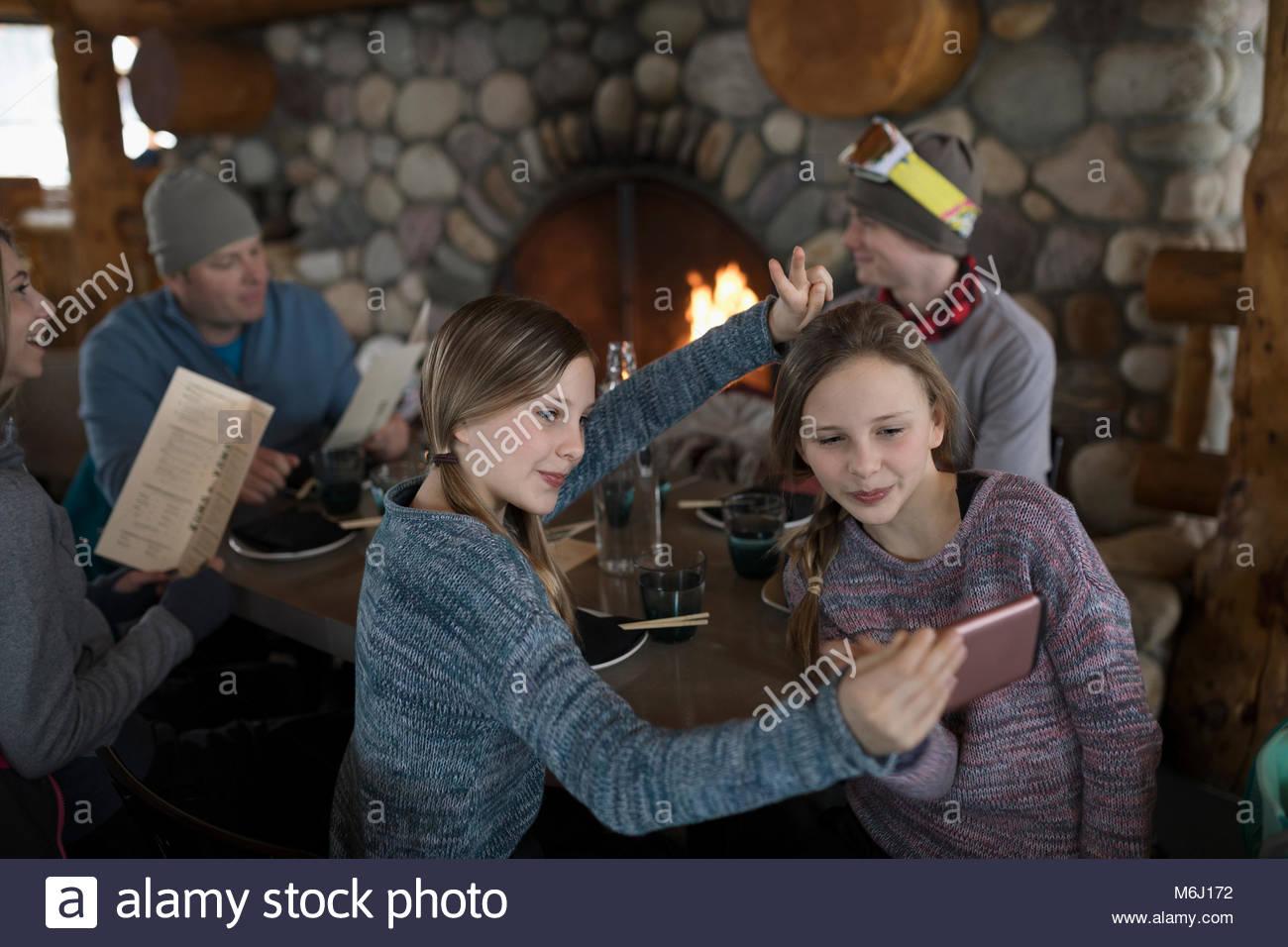 Twin sister skiers taking selfie at fireside ski resort lodge apres-ski - Stock Image