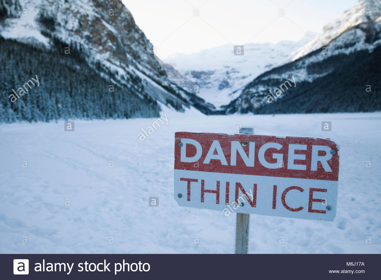 Danger Thin Ice sign on snowy mountain lake - Stock Image