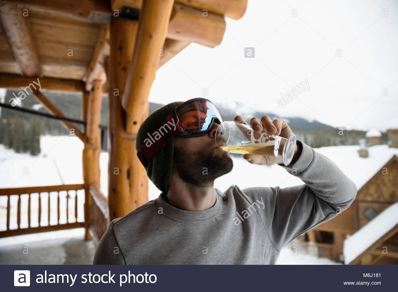 Male skier in ski goggles enjoying apres-ski, drinking beer on snowy ski resort lodge balcony - Stock Image