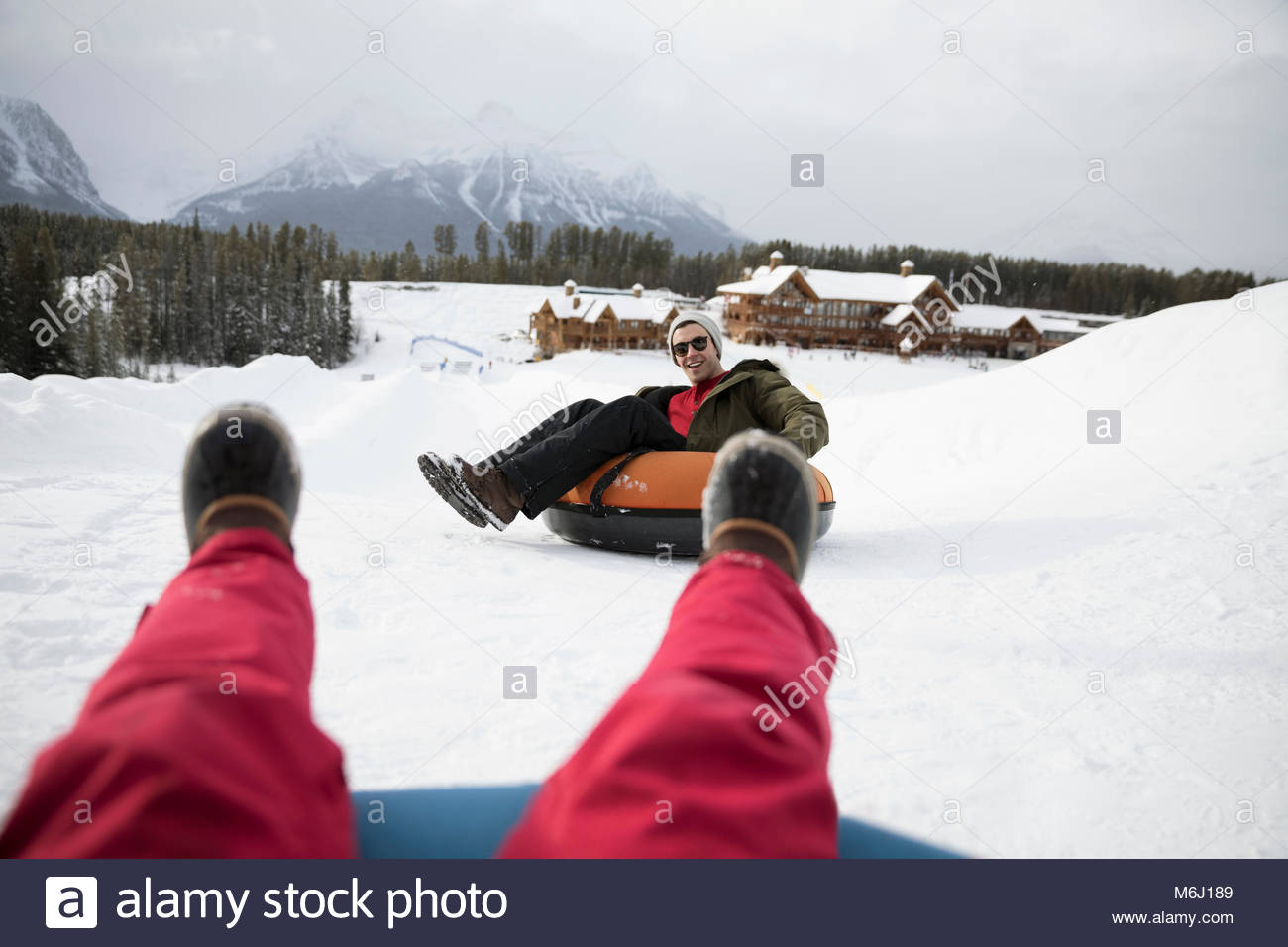 Personal perspective friends riding inner tubes in snow outside ski resort - Stock Image