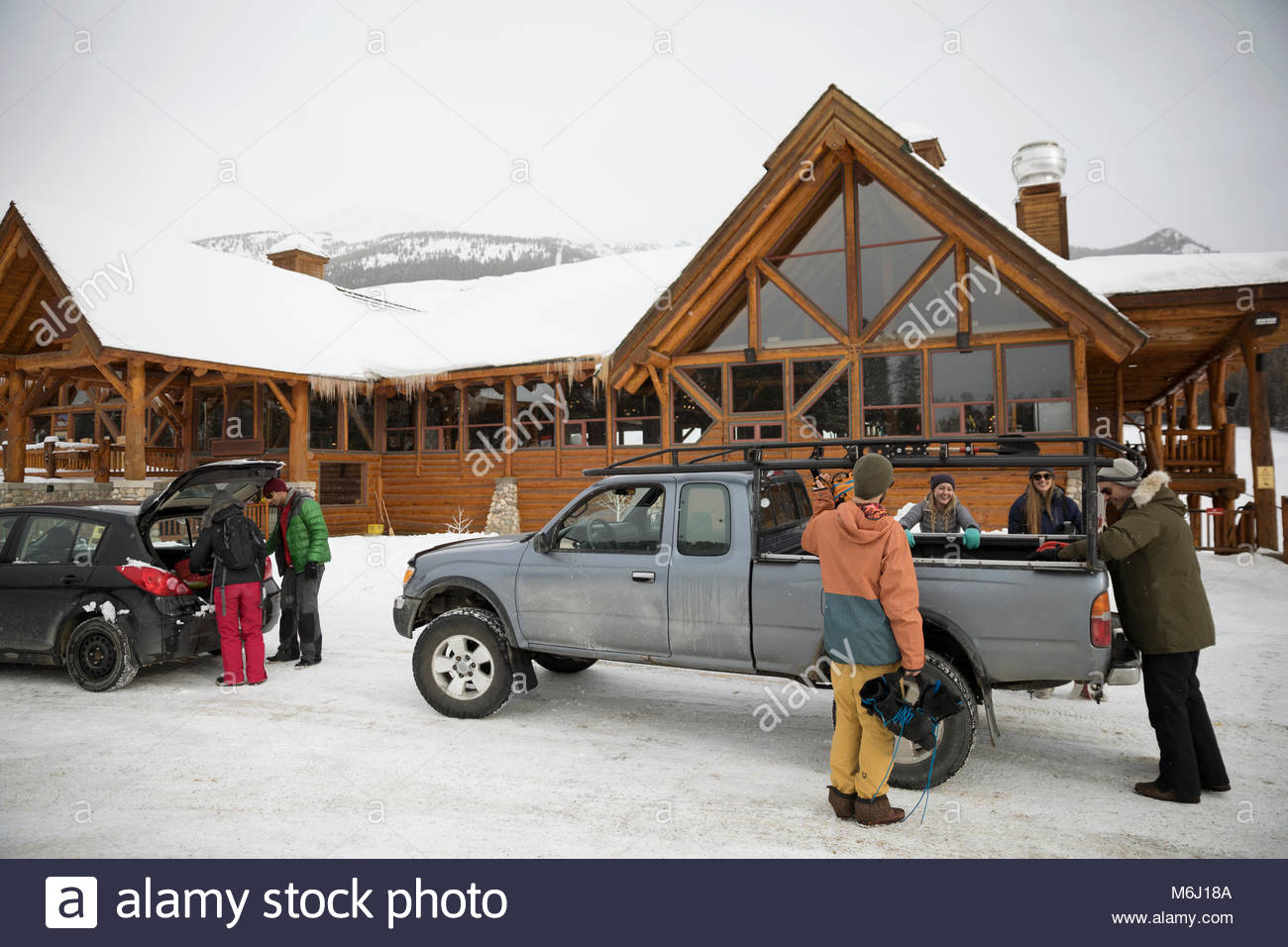 Friends unloading snowboarding and skiing equipment from car and truck at snowy ski resort - Stock Image