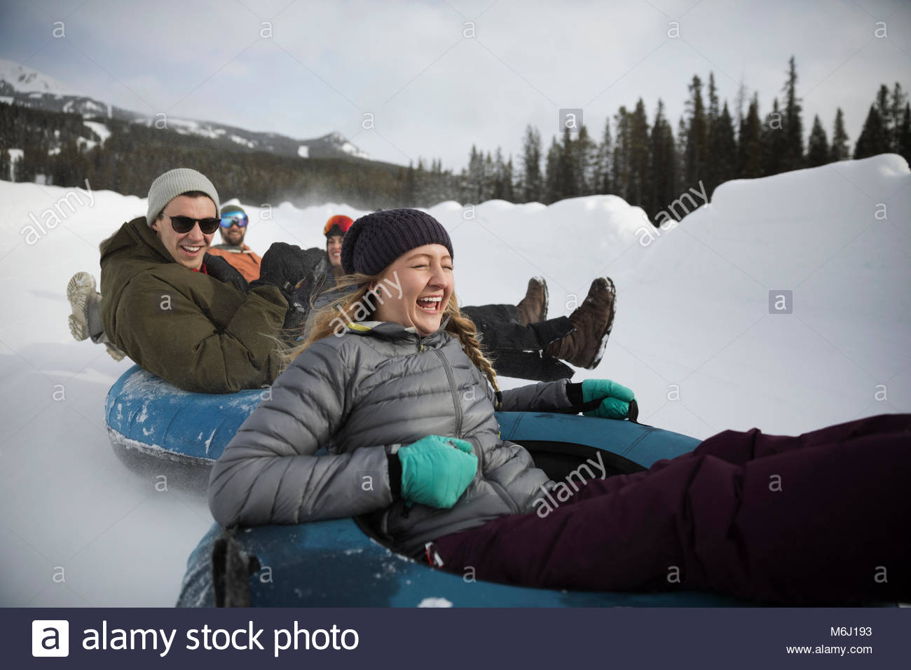 Playful, happy friends riding inner tubes in snow - Stock Image
