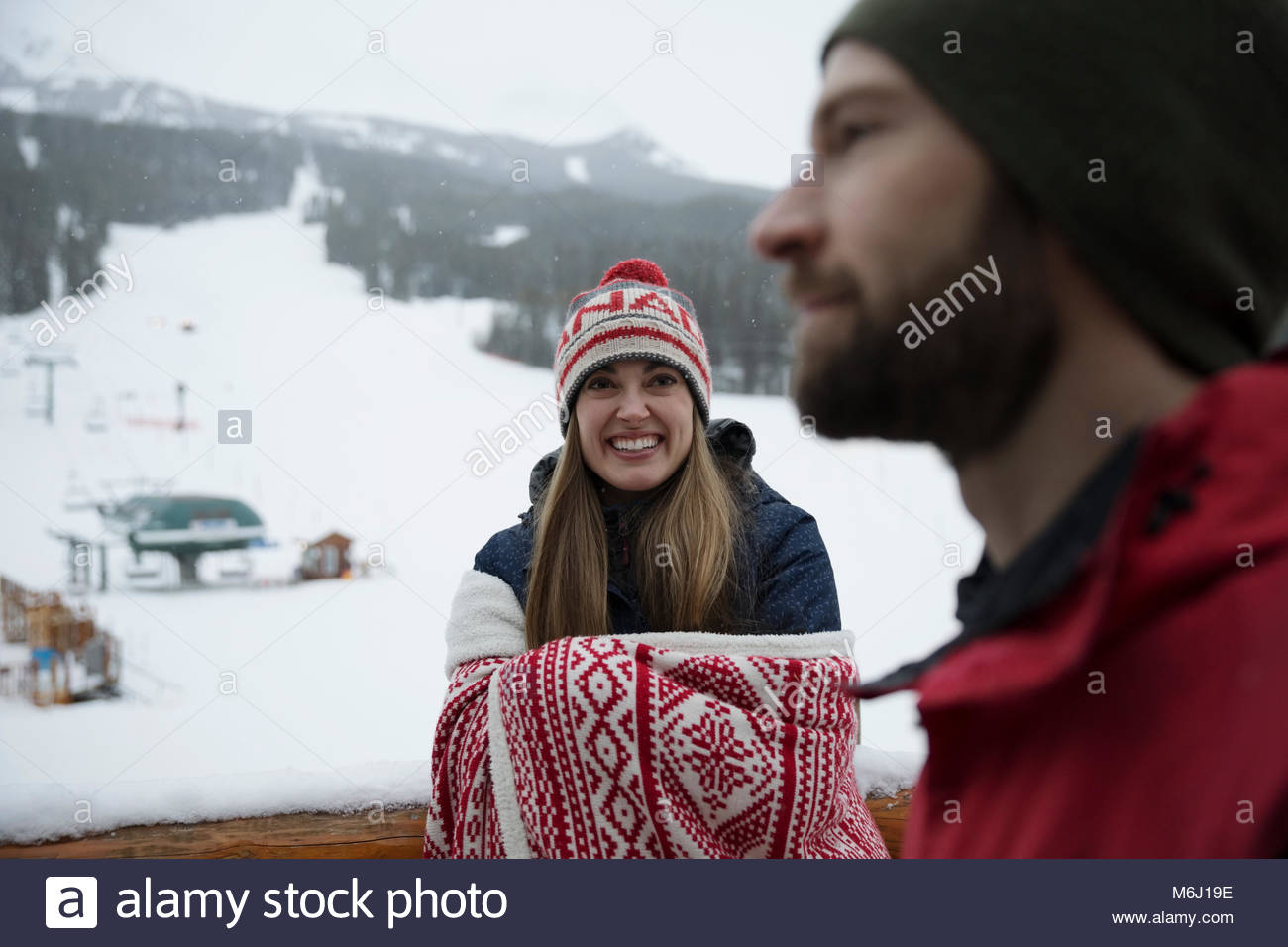 Smiling woman wrapped in a blanket on snowy ski resort balcony - Stock Image