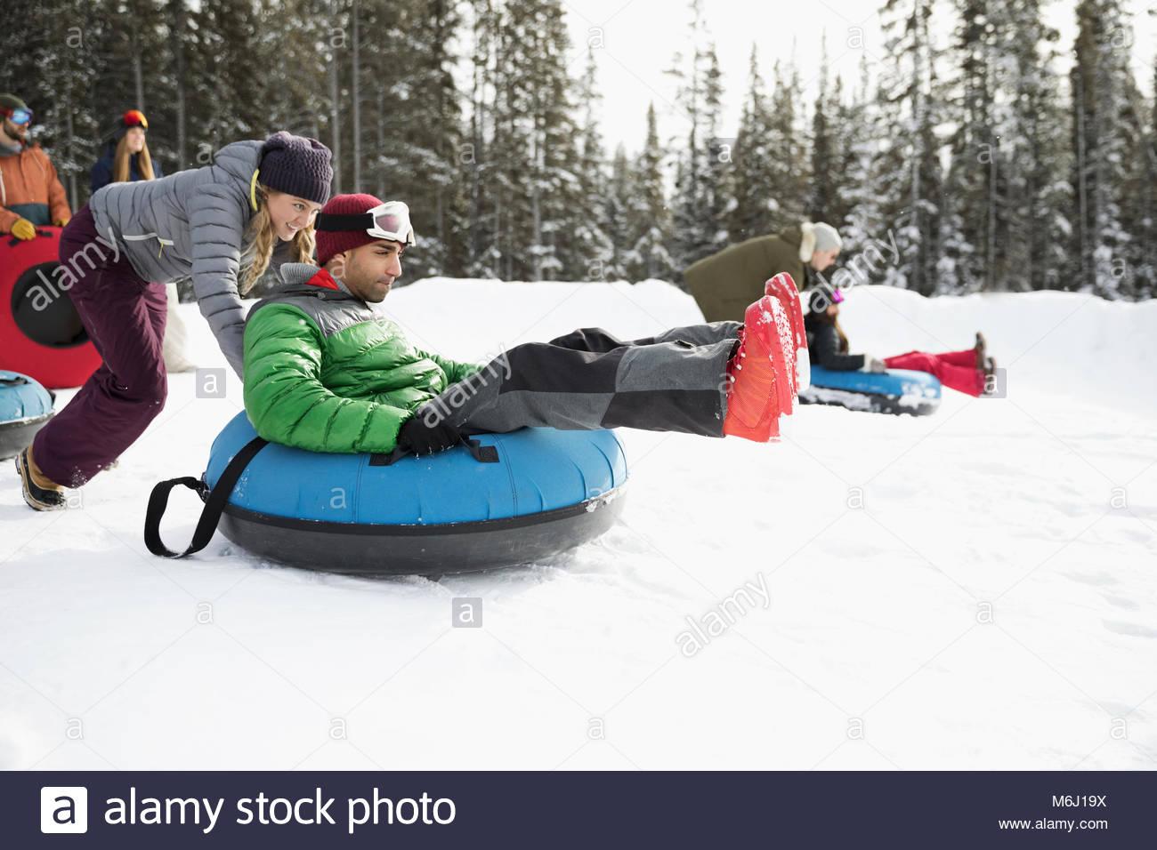 Friends racing, inner tubing in snow - Stock Image