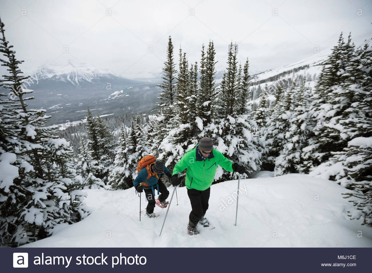 Friends snowshoeing, climbing snowy mountain hill - Stock Image