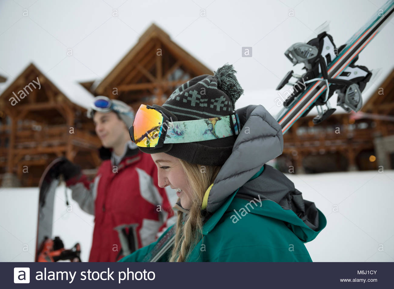 Smiling young female skier carrying skis outside ski resort lodge - Stock Image