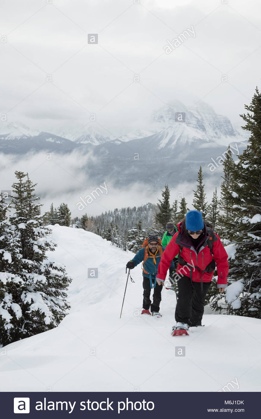 Friends snowshoeing up snowy hill - Stock Image