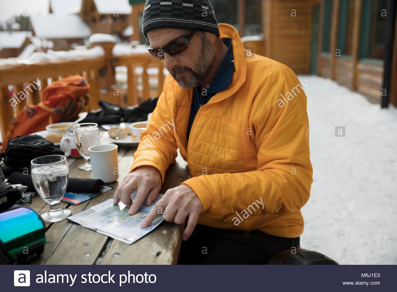 Male skier enjoying breakfast, preparing with map on snowy ski resort balcony Stock Photo