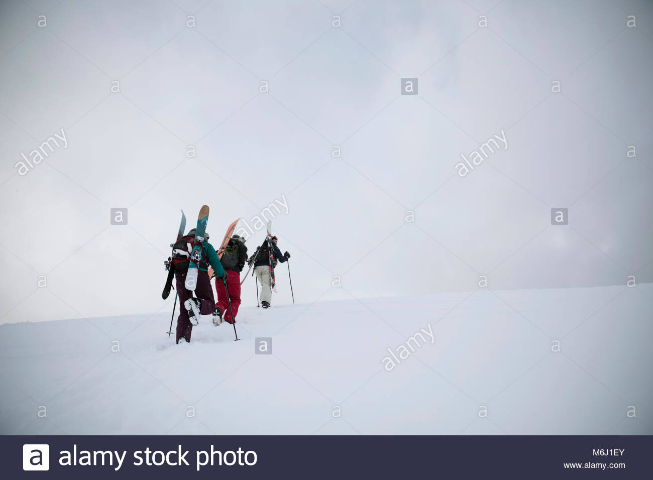 Female skier and snowboarder friends hiking up snow covered hill - Stock Image