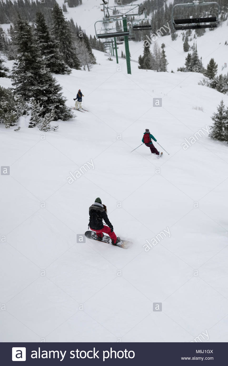 Snowboarder and skiers skiing snowy slope - Stock Image