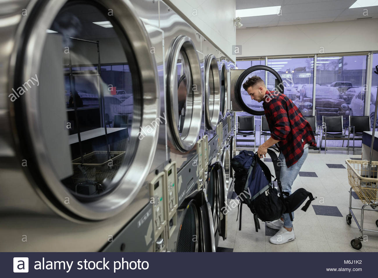 Young man with backpack doing laundry at laundromat - Stock Image
