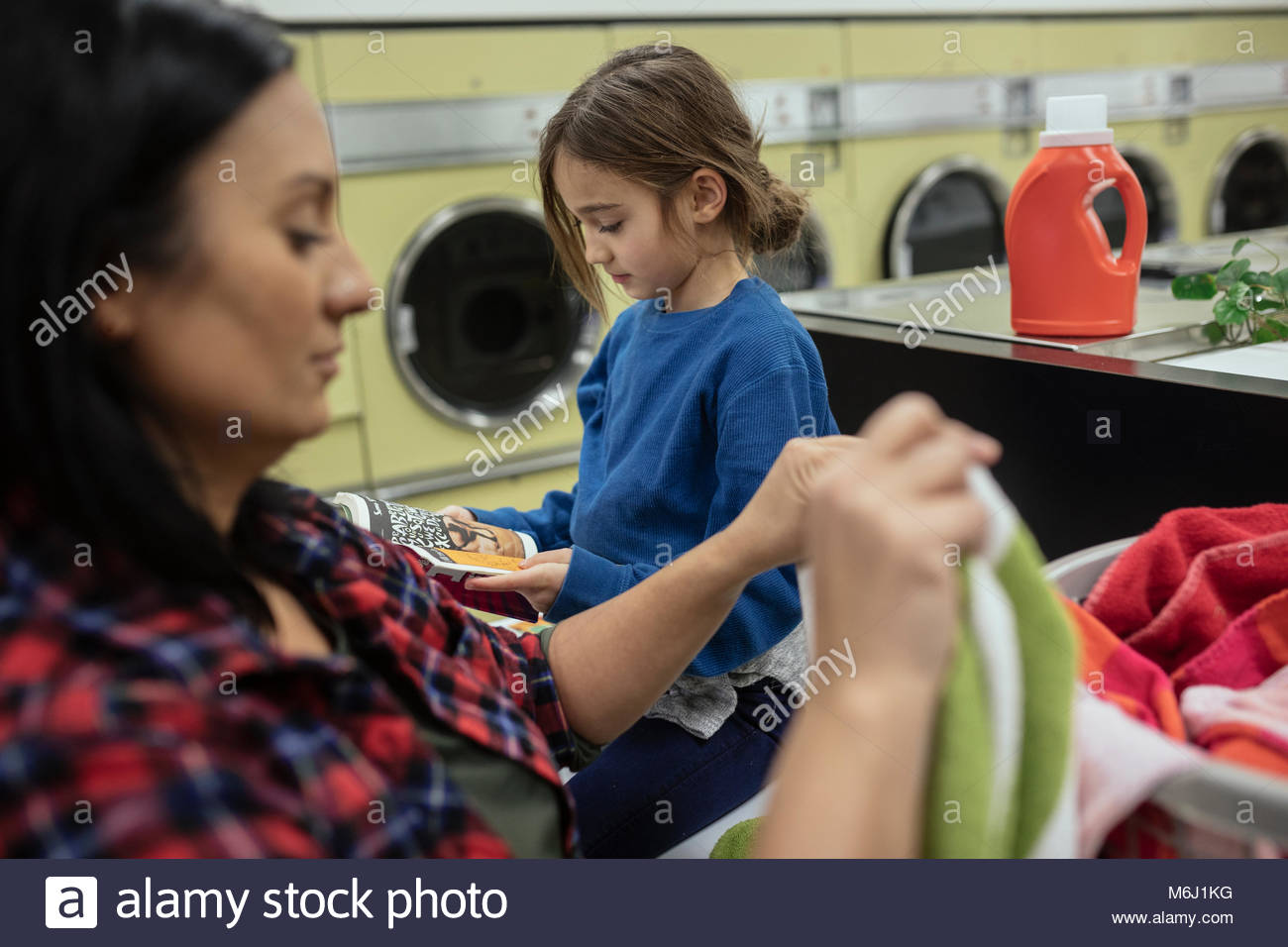 Mother and daughter doing laundry at laundromat - Stock Image