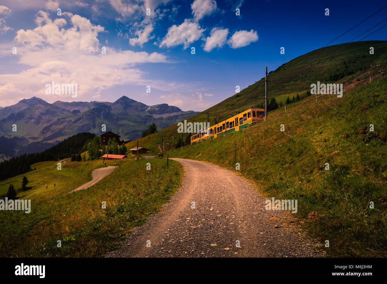 Colorful landscape in the Jungfrau region with the mountain train from Lauterbrunnen to Kleine Scheidegg. Wengen, Stock Photo