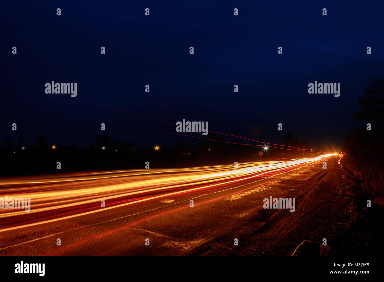 Photos of Ukrainian roads under the evening sky, on which cars are moving and blurring the way with their light - Stock Image
