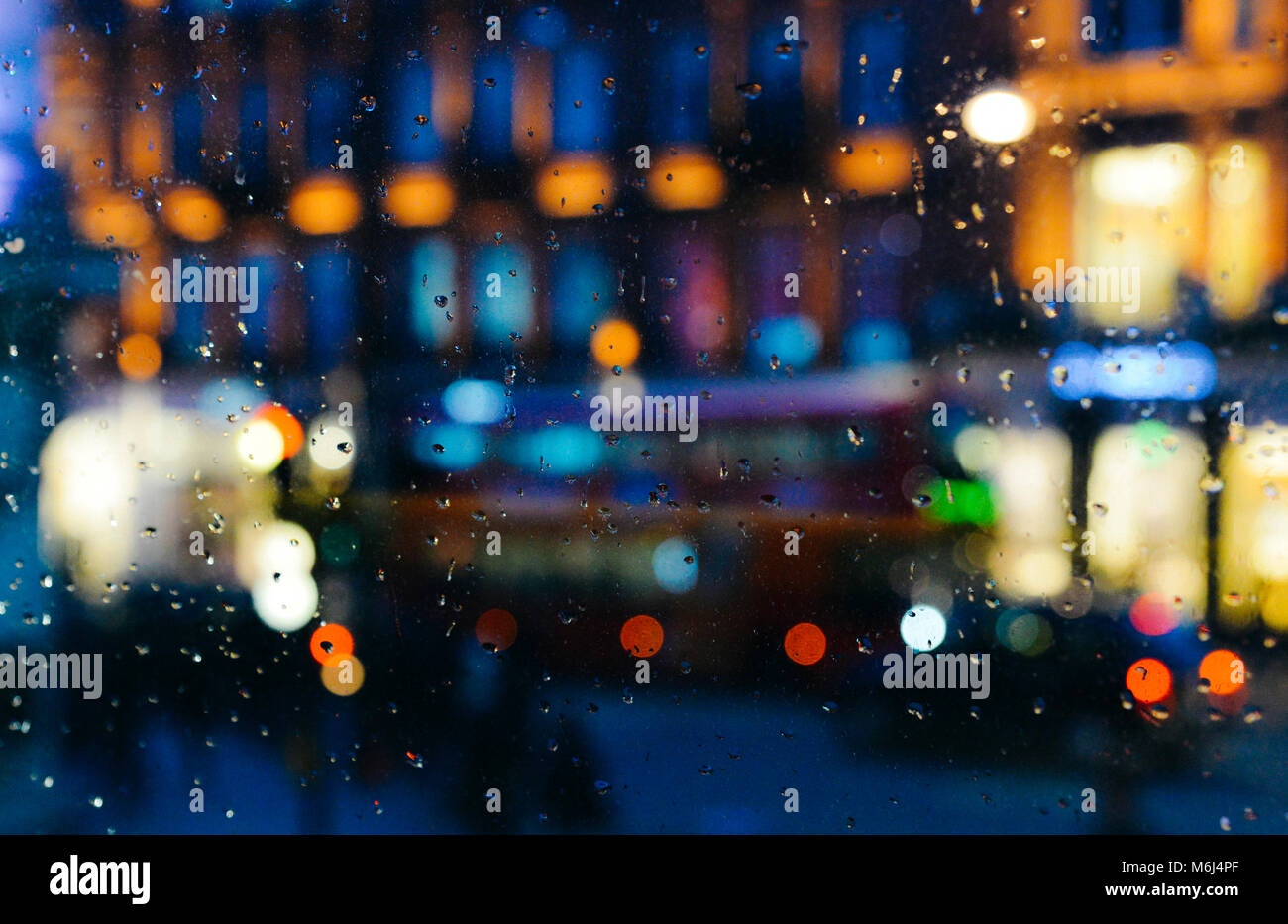 Emotional melancholic abstract background with defocused lights bokeh in London, UK behind rain drops in window - Stock Image