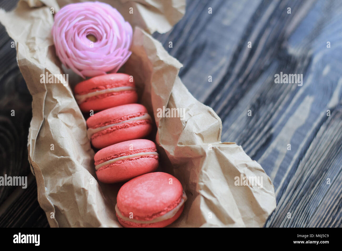 Colorful macaroons and flowers on table - Stock Image