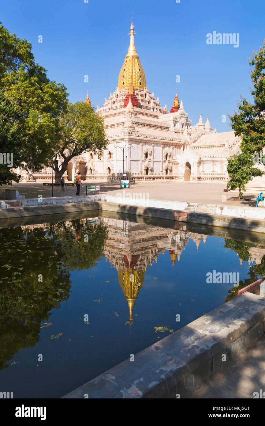 Tourists at Ananda Pagoda, Ananda Temple at Bagan, Myanmar (Burma), Asia in February - reflected in water - Stock Image