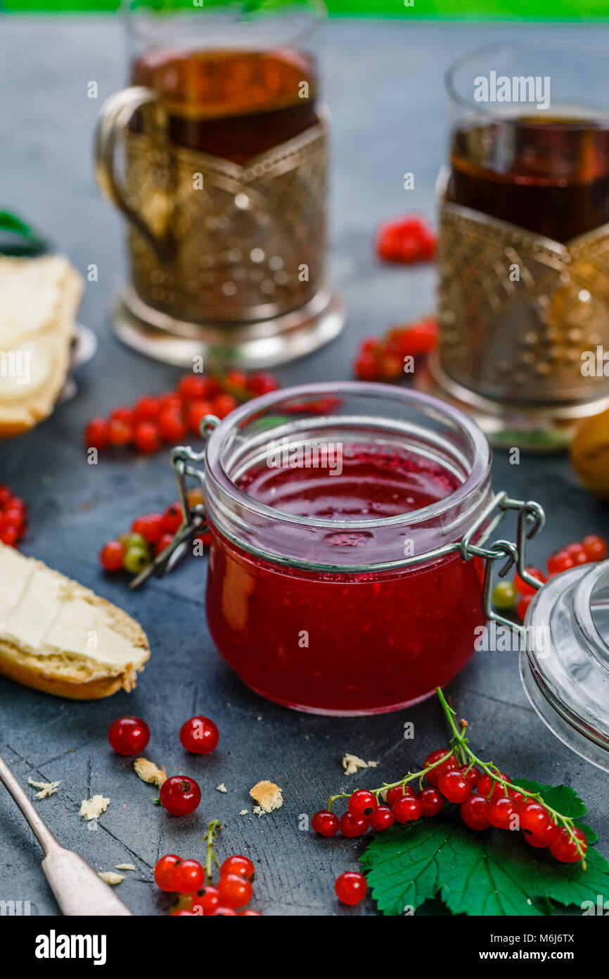 Red currants and jar of jam in garden - Stock Image