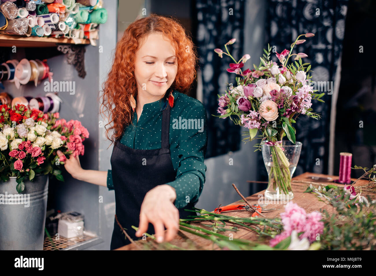 snapshot of good-looking floral assistant counting flowers for bouquet - Stock Image