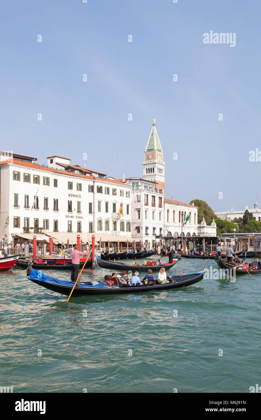 Several gondolas with tourists in the Grand Canal, Basino San Marco near the San Marco vaporetto stop, Venice, Italy - Stock Image
